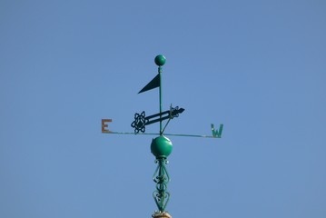 Green metal weathervane against cloudless blue sky