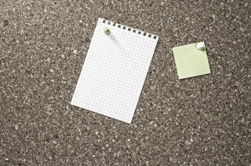 two blank paper notes on a board
