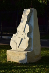 A stone monument featuring a violin