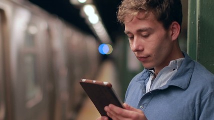 Young caucasian man in city using tablet pc subway
