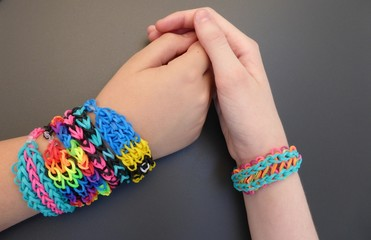 Loom band friendship bracelets on girls' forearms