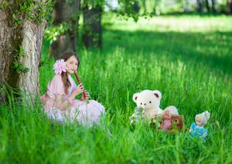 Девочка в розовом платье играет на флейте любимым игрушкам