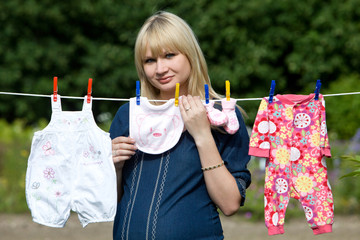 Pregnant woman with baby clothes. Baby clothes on a clothesline.