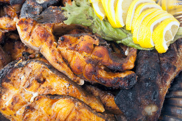 Grilled fish fillet on barbecue with lemons wedges