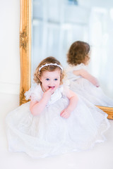 Little girl in a white dress next to a mirror