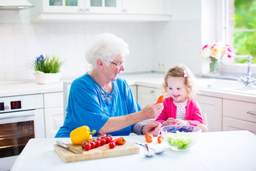 Grandmother and cute girl making salad