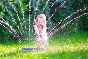 Happy girl playing with garden sprinkler