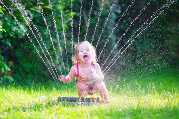 Funny girl playing with garden sprinkler