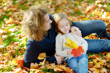 Father and his daughter sitting on maple leaves