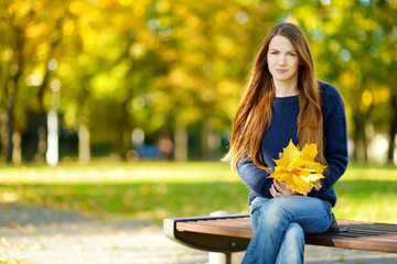 Beautiful young woman having fun on autumn day