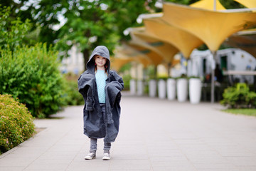 Funny little girl wearing her fathers' coat