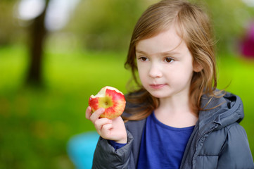 Cute little preschooler girl eating an apple
