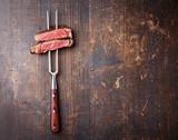 Slices of beef steak on meat fork on dark wooden background
