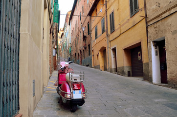Vintage scene with Vespa on old street, siena, italy