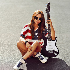 Young beautiful woman with electric guitar - outdoors