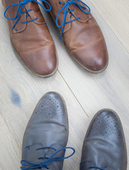 two pairs of shoes toe to toe on  a wooden floor