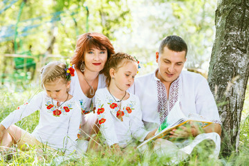 Beautiful family reading book together in park