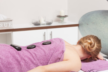 Beauty salon. Woman getting spa hot stone therapy massage