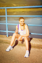 Young runner woman with smartphone making music playlist