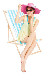 young sunshine girl smiling and sitting on a beach chair