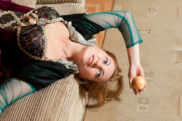 actress with an apple in medieval dress lies on a background of