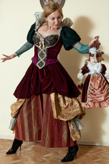 actress in medieval dress is holding a doll's hair in the interi
