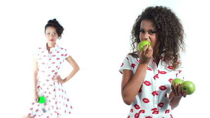 African teenage girl biting green apple on white background
