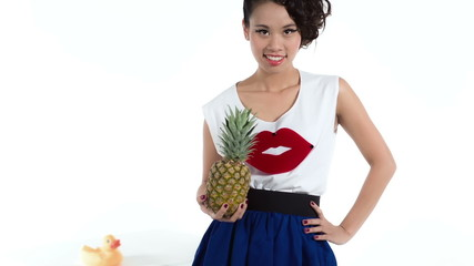 Cheerful asian model with a pineapple posing in studio