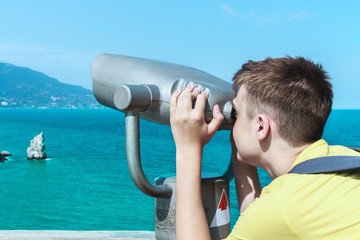 man looking through binoculars at the mountains and the sea