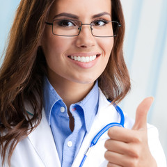Doctor showing thumbs up gesture, at office