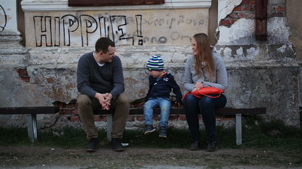 Parents and their child sitting on the bench near old grungy