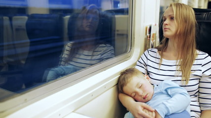 Woman looking out the train window with her son sleeping on the