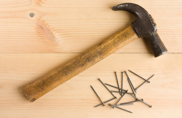 Old hammer and iron nails on wooden floor