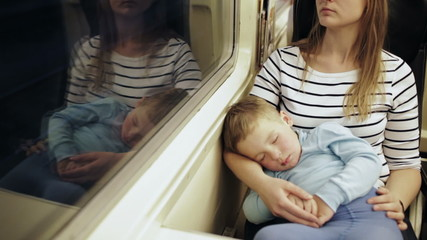 Tired woman in the train with sleeping son on her lap