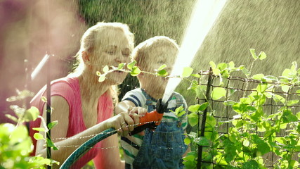 Mom and son watering the garden together