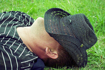 Man has a rest on the grass covered with a hat