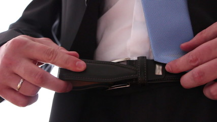 Businessman/diplomat/groom in elegant suit adjusting his belt