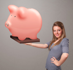 Young girl holding a huge savings piggy bank