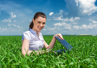 girl with notebook on green field