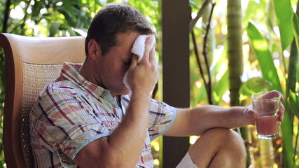 Man wiping sweat from face and drinking juice in the garden