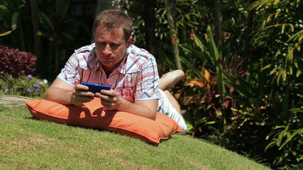 Man lying on grass in the garden and tweeting on cellphone
