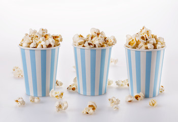 Buttered popcorn in striped paper cups over white background