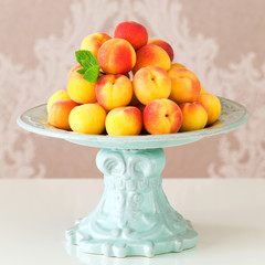 Ripe fresh apricots in a vase on table, selective focus