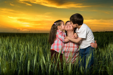 happy family at sunset. child kissing mom