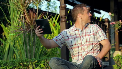 Man sitting in the garden and chatting on tablet