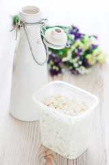 Cottage cheese and milk bottle on the table, selective focus