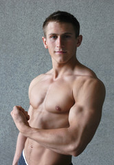 Young muscular man flexing his biceps