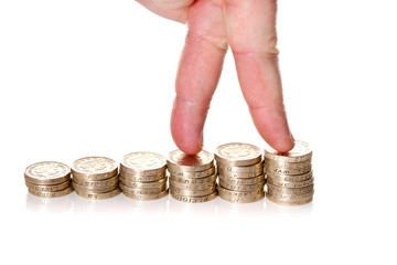 Fingers walking up on stacks of one pound coins