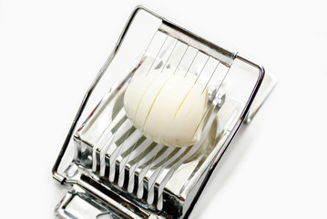 Slicing a Hard Boiled Egg Isolated on White