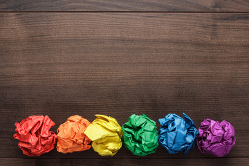 crumpled colorful paper on wooden background